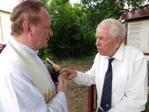 Paul Stronk (rechts) an der von ihm gespendeten Tafel im Gespräch mit Minderheitenseelsorger Peter Tarlinski.  Bild: Klaudia Kandzia